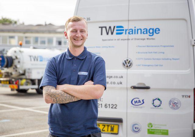 tw drainage employee standing infront of van
