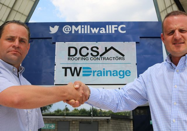 two men shaking hands infront of millwall fc sign